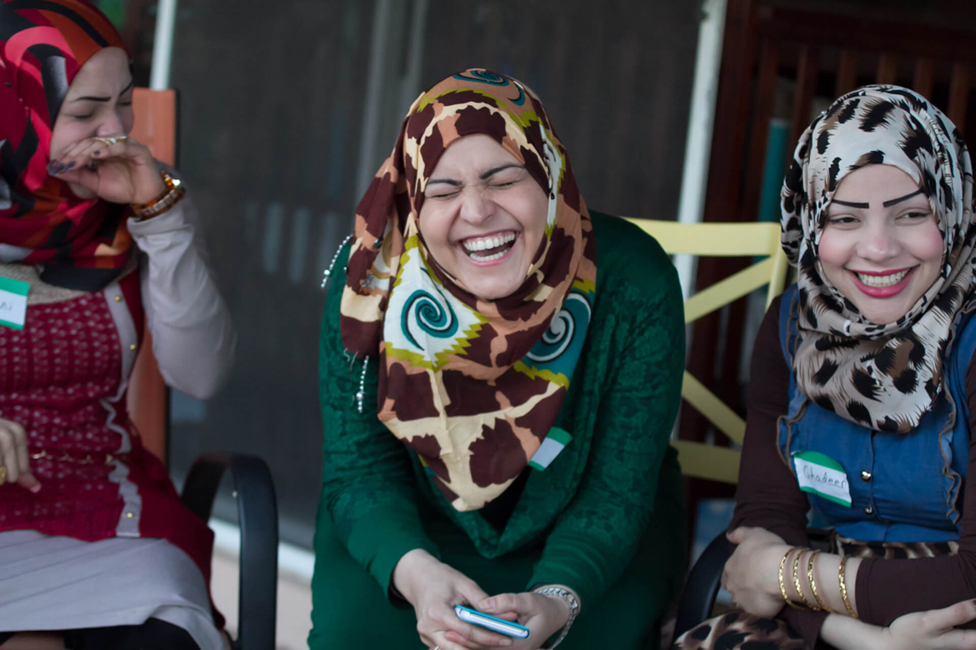 Two sisters and a friend share a laugh at a welcome party for the woman to the far right who had been separated from her sister and kin for 4 years due to being in a refugee camp.