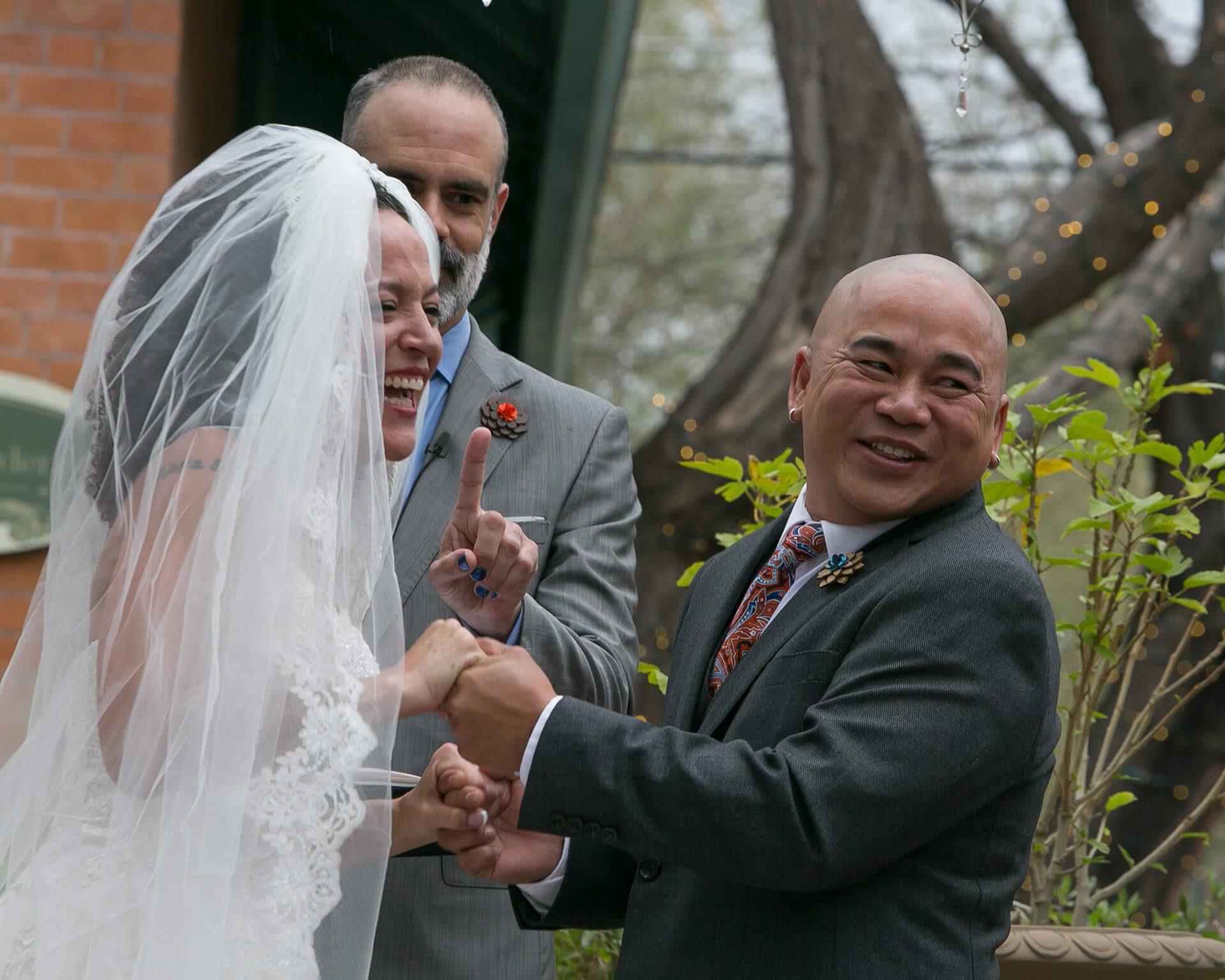 The minister jokingly admonishs the groom who tries to kiss his bride prematurely in the ceremony. The couple and their guests laughed with joy and playfulness.