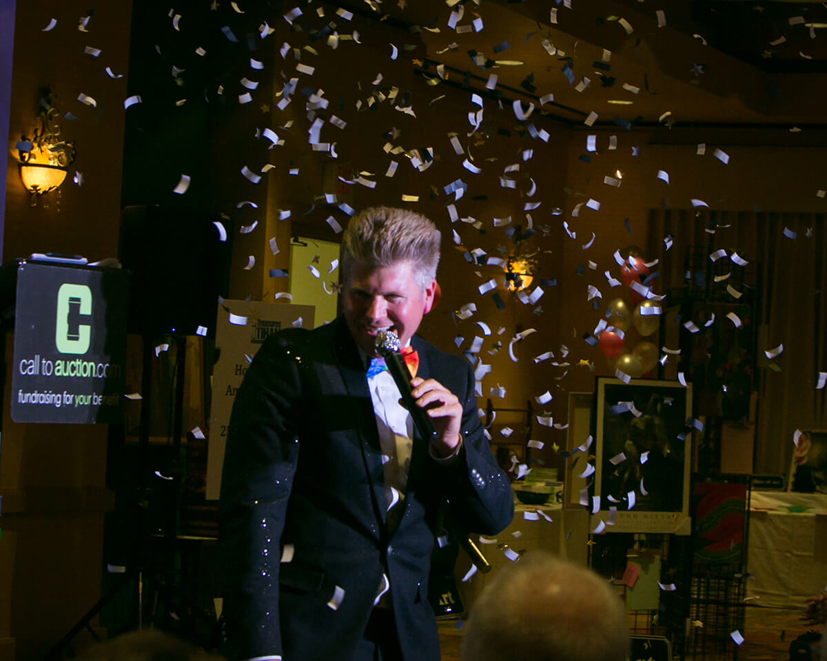 The Master of Ceremonies is awash in confetti following a sucessful auction for TIHAN (Tucson Interfaith HIV/AIDS Network)