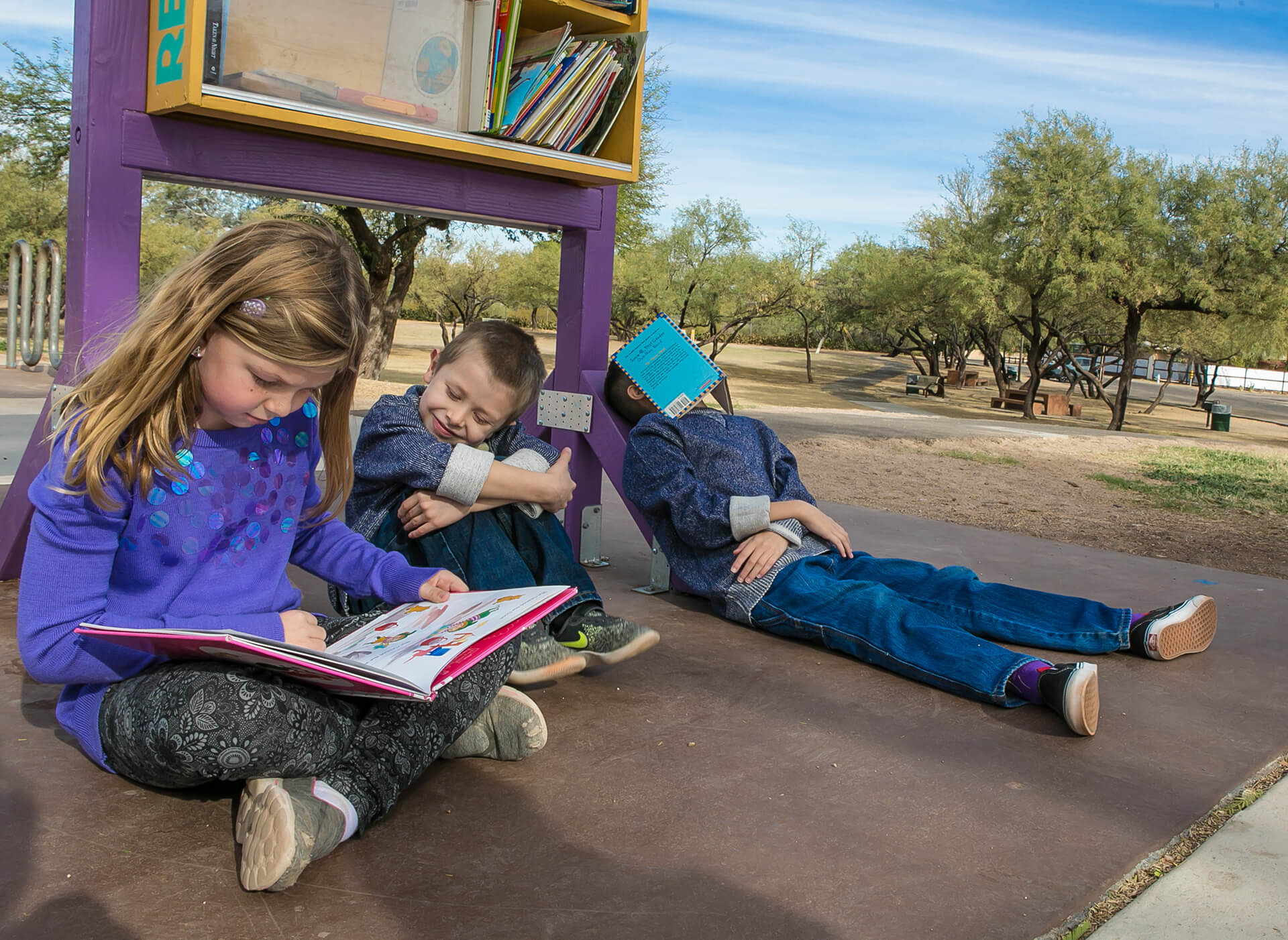 """Kathleen often uses environmental features available during the family session as spontaneous portrait props. Kathleen gave the children a simple prompt to do whatever they like with the free """"library"""" at the park and this is the result."""