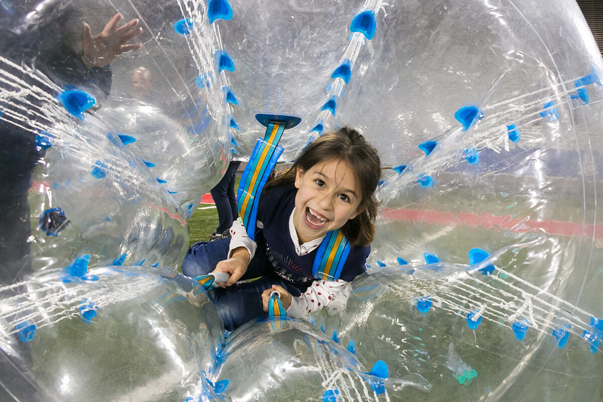 """A child delights in being rolled in a """"hamster ball"""" during a company holiday party."""