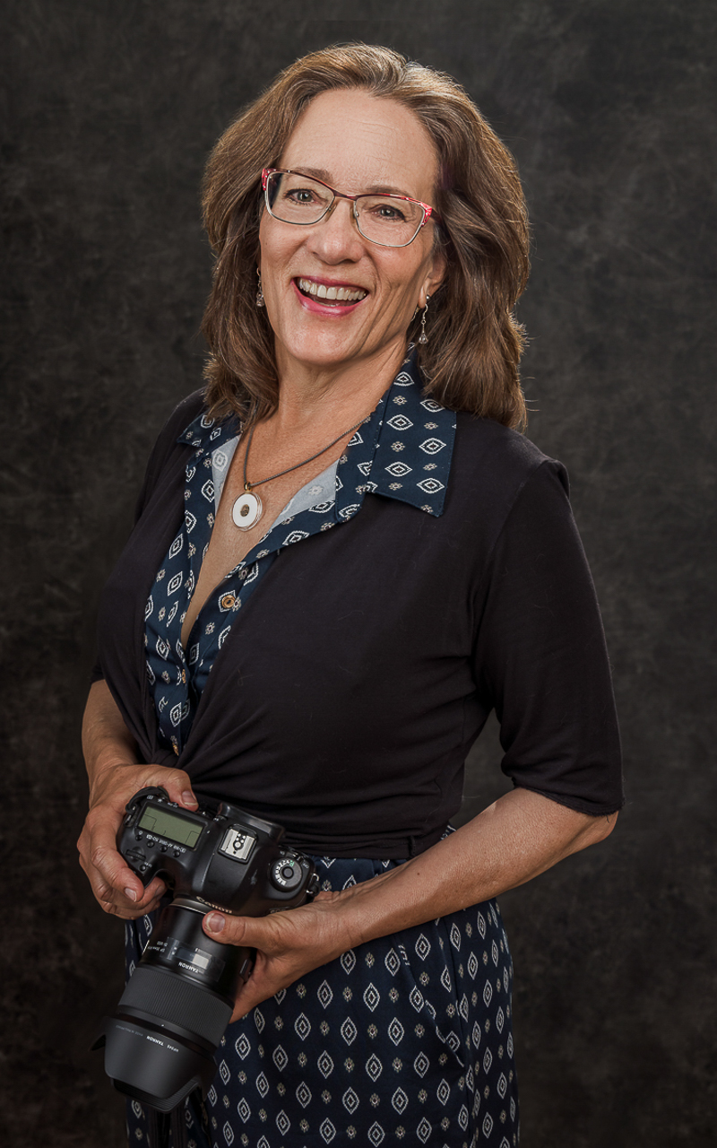 A white woman with shoulder-length hair, standing holding her camera in both hands. She is wearing a diamond-pattern jumpsuit withe a 3/4 sleeve black over wrap.