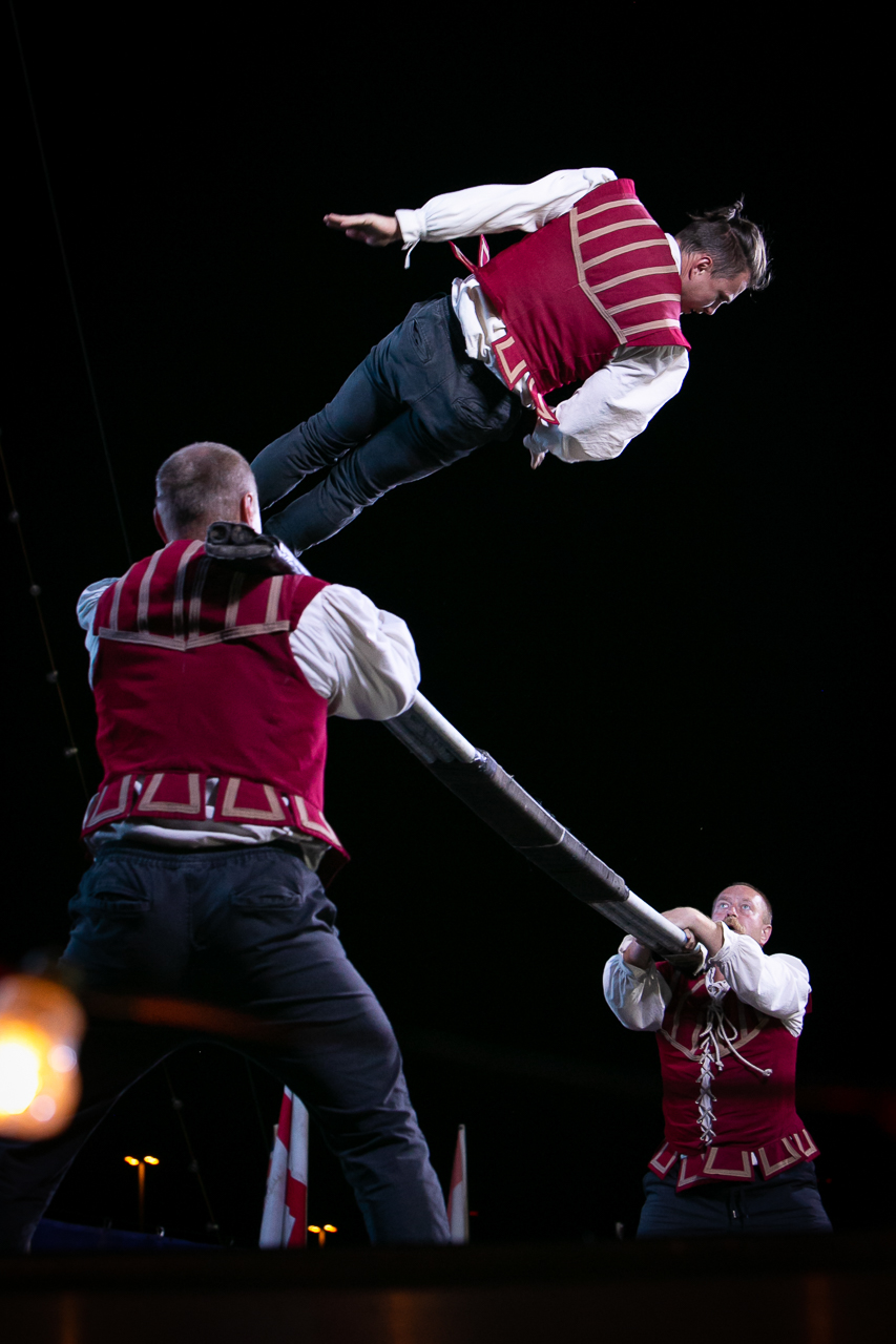 Two men holding a long pole between them while a third man flies in the air above them propeled by the two men below him.