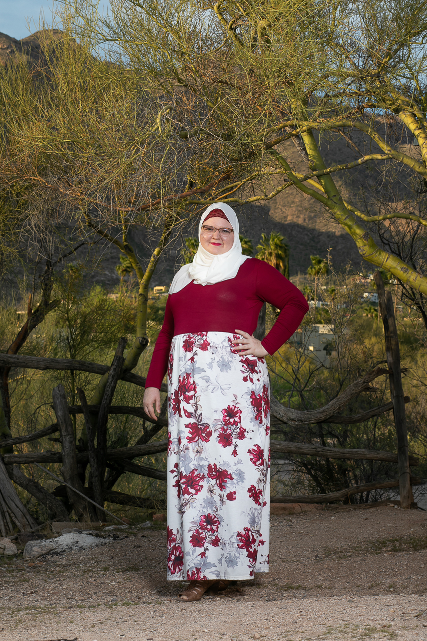 White woman wearing a flower print floor-length skirt, deep red long sleeve blouse and a white hijab standing in front of a palo verde tree.