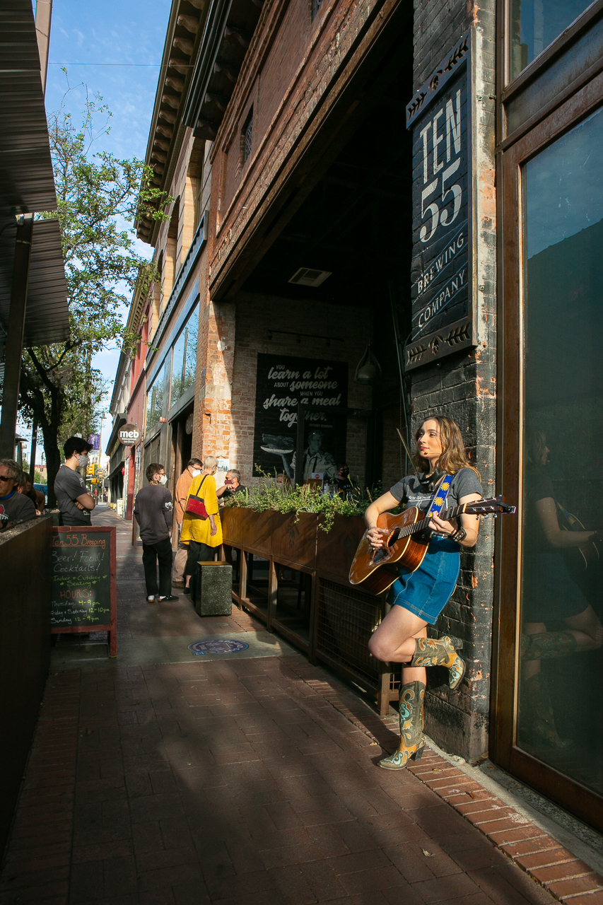 A young adult woman with long brown hair, short blue jean skirt and cowboy boots, plays her guitar while leaning against a building.