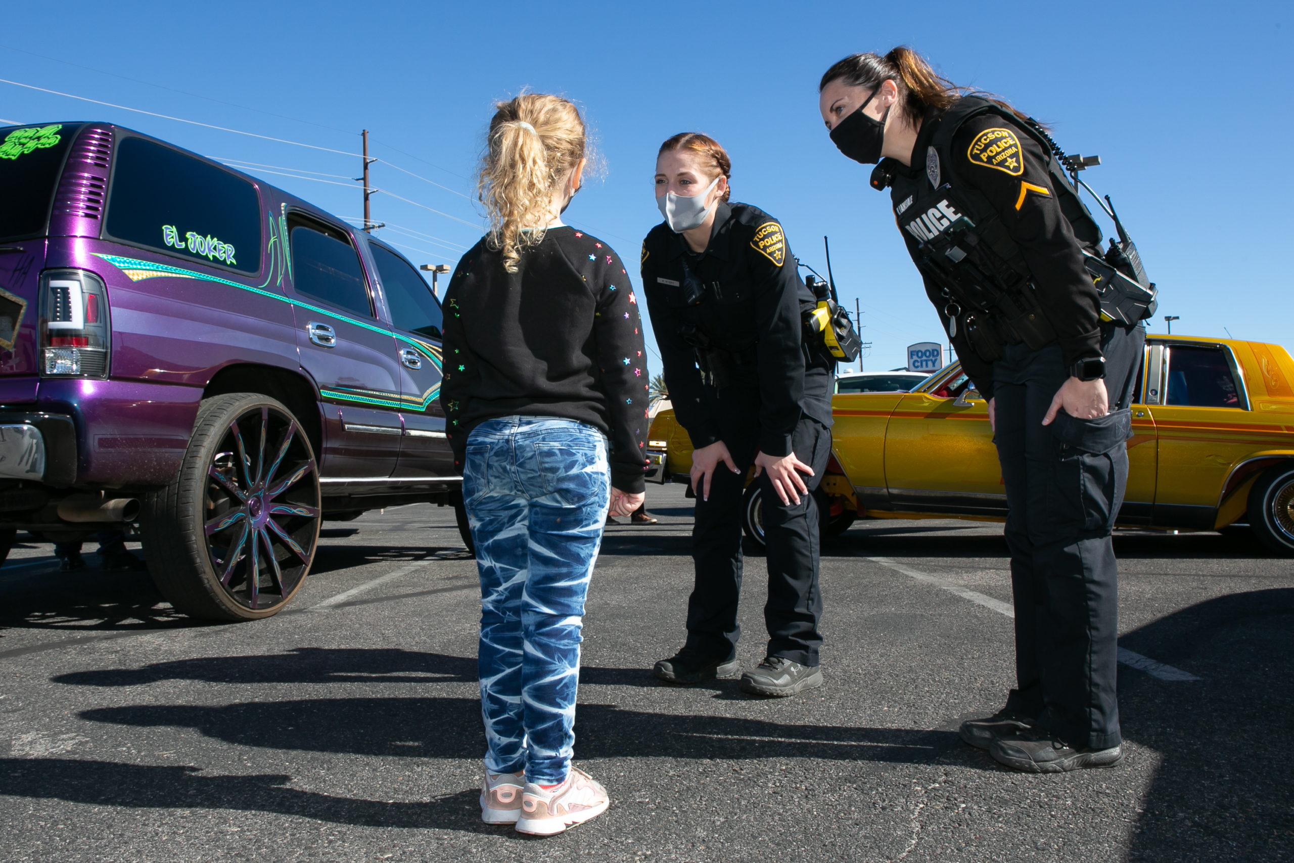 A white girl with her blond hair in a ponytail looks up at 2 female officers who bend at the waist to speak to the girl more so at her eye level.